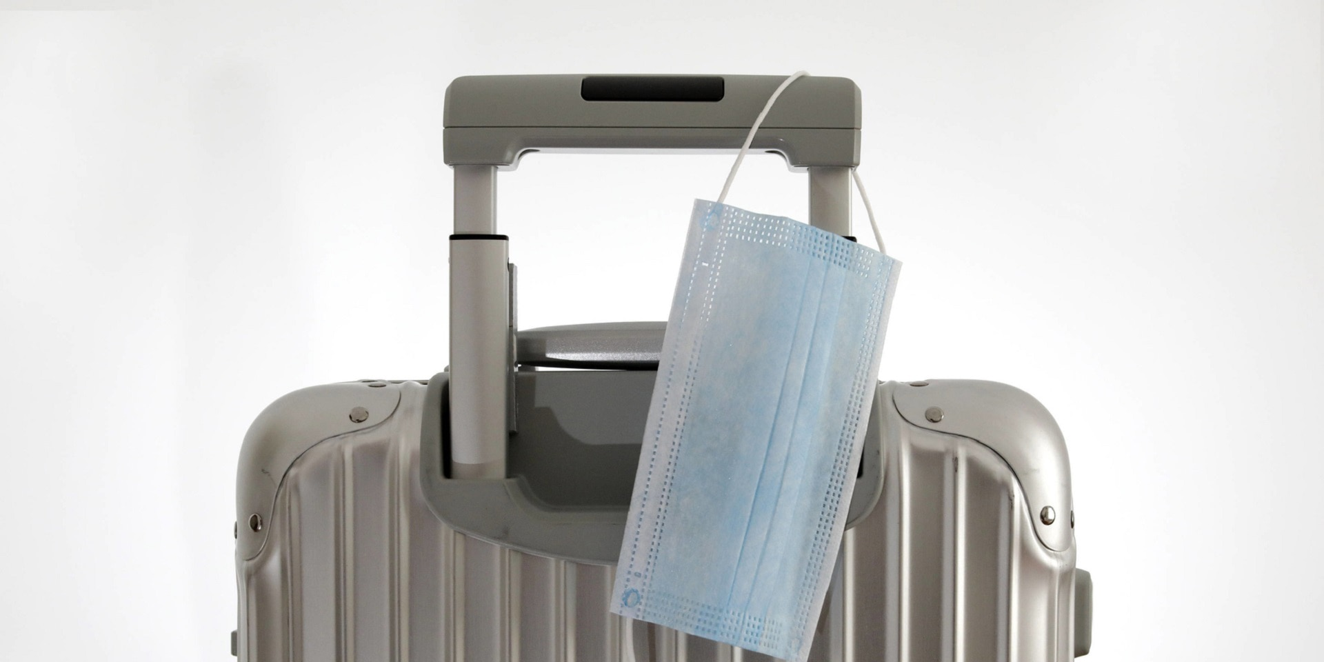 A face mask hangs on the handle of a gray suitcase.