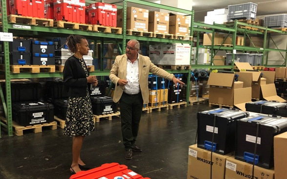 SDC Director Patricia Danzi walks through the depot with HA Logistics Manager Markus Hischier and looks at the material.