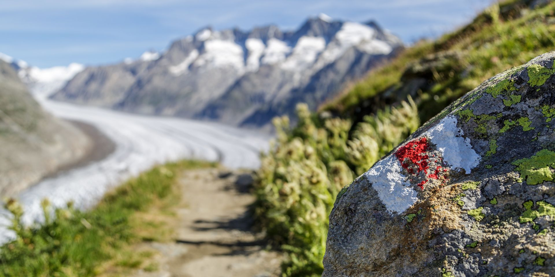 The photo shows a hiking trail in the canton of Valais, with the Aletsch Glacier in the background.