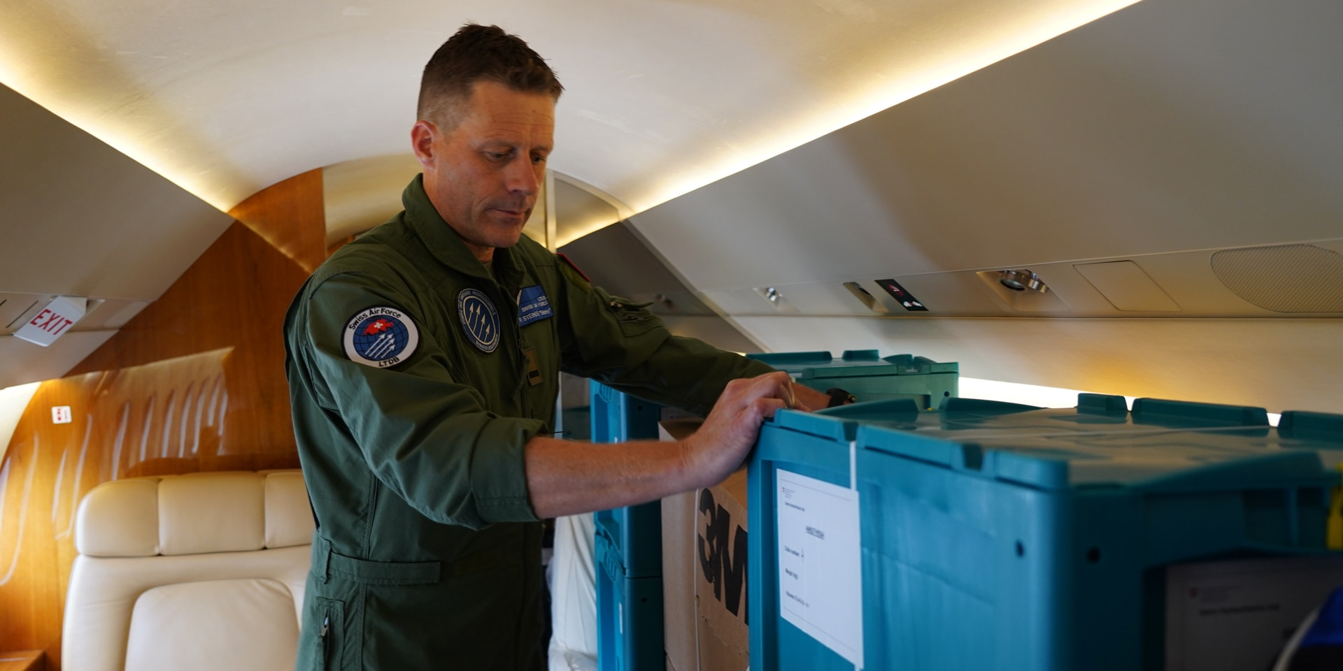 A pilot inside an aircraft checking that boxes of relief supplies are securely fastened.