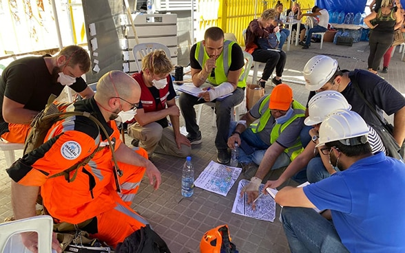 Experts from the Swiss Humanitarian Aid Unit discuss a map of the area.