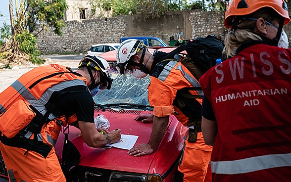 Three experts from the Swiss Humanitarian Aid Unit discuss an action plan on the hood of a broken-down vehicle.