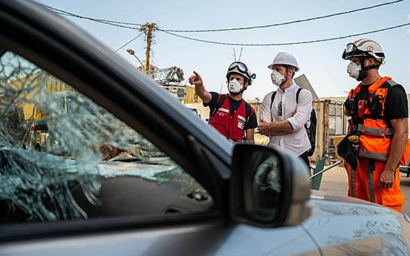 View through a broken vehicle window at three experts of the Swiss Humanitarian Aid Unit.