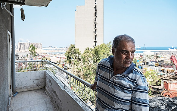 A man stands on the balcony of his broken-down apartment block and looks out over the city.