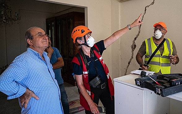 An expert from the Swiss Humanitarian Aid Unit discusses with a resident the damage to his home.