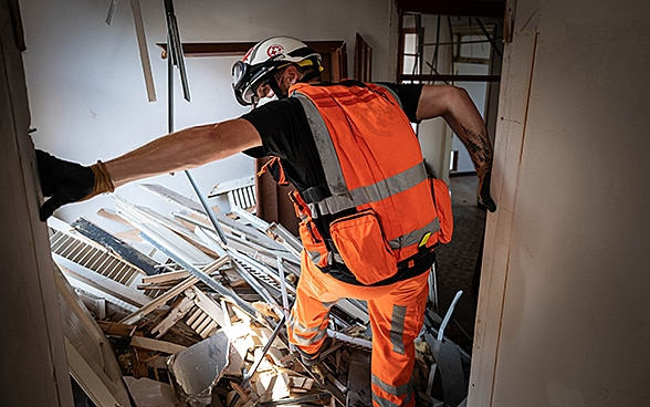 An expert from the Swiss Humanitarian Aid Unit is climbing over debris in a house.