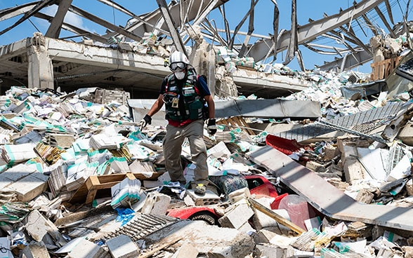 An expert of the Swiss Humanitarian Aid Unit descends from a pile of debris. Among other things, vehicles and parts of buildings can be seen.