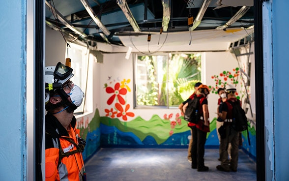An expert from the Swiss Humanitarian Aid Unit looks at the damaged ceiling of a hospital.