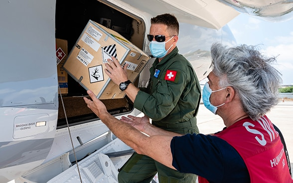 View of a Swiss Air Force pilot loading a container from an aircraft together with an expert from the Swiss Humanitarian Aid Unit.