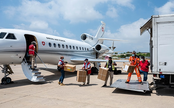 View of several experts from the Swiss Humanitarian Aid Unit form a human chain to transfer material from an aircraft to a truck.