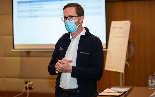 An expert from the Swiss Humanitarian Aid Unit provides information at a situation briefing.
