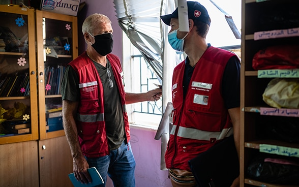 Two experts from the Swiss Humanitarian Aid Unit are talking in a destroyed classroom.
