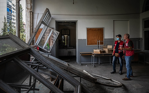 Two experts from the Swiss Humanitarian Aid Unit look out of a broken wall of a classroom.