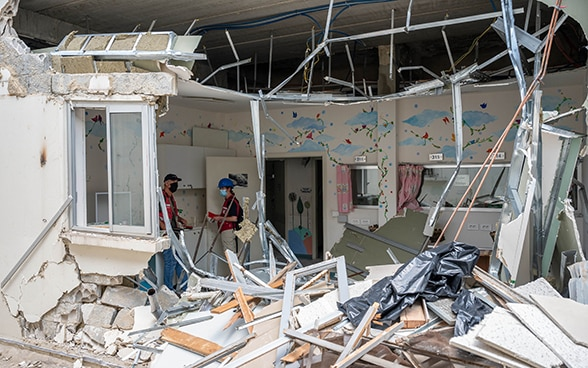 Two experts from the Swiss Humanitarian Aid Unit are standing in the destroyed hospital in the Karantina district.