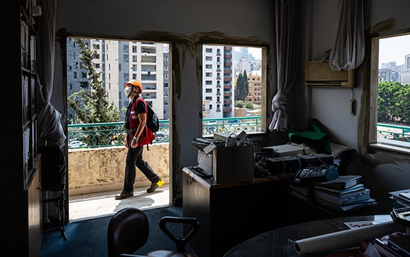 View from a demolished apartment without windows. Engineer Regina Wenk is walking on the balcony and looking at the damage.