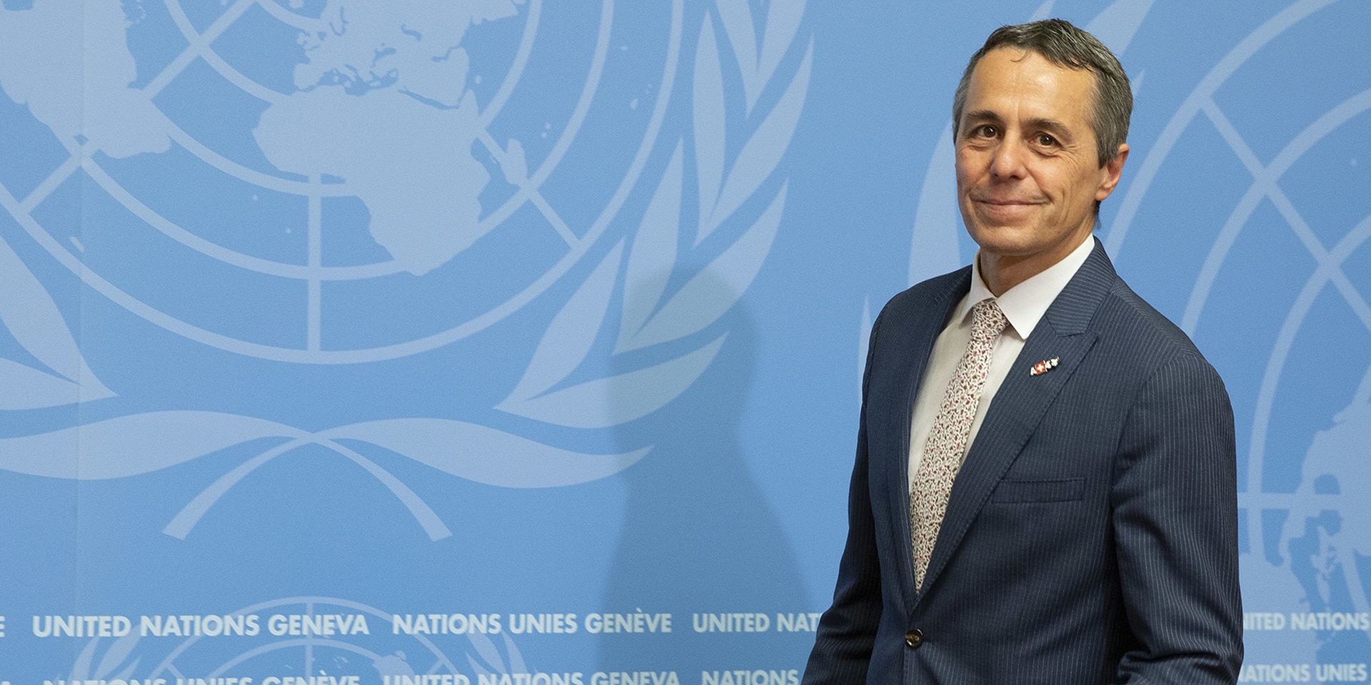 Federal Councillor Ignazio Cassis stands in front of a podium, behind him a wall with the UN logo.