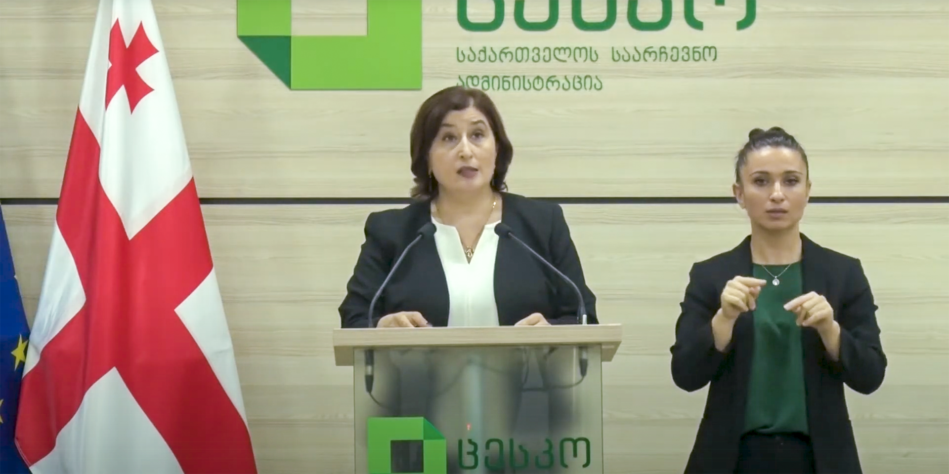The head of the Central Election Commission in Georgia is at a desk, next to her a specialist in sign language.