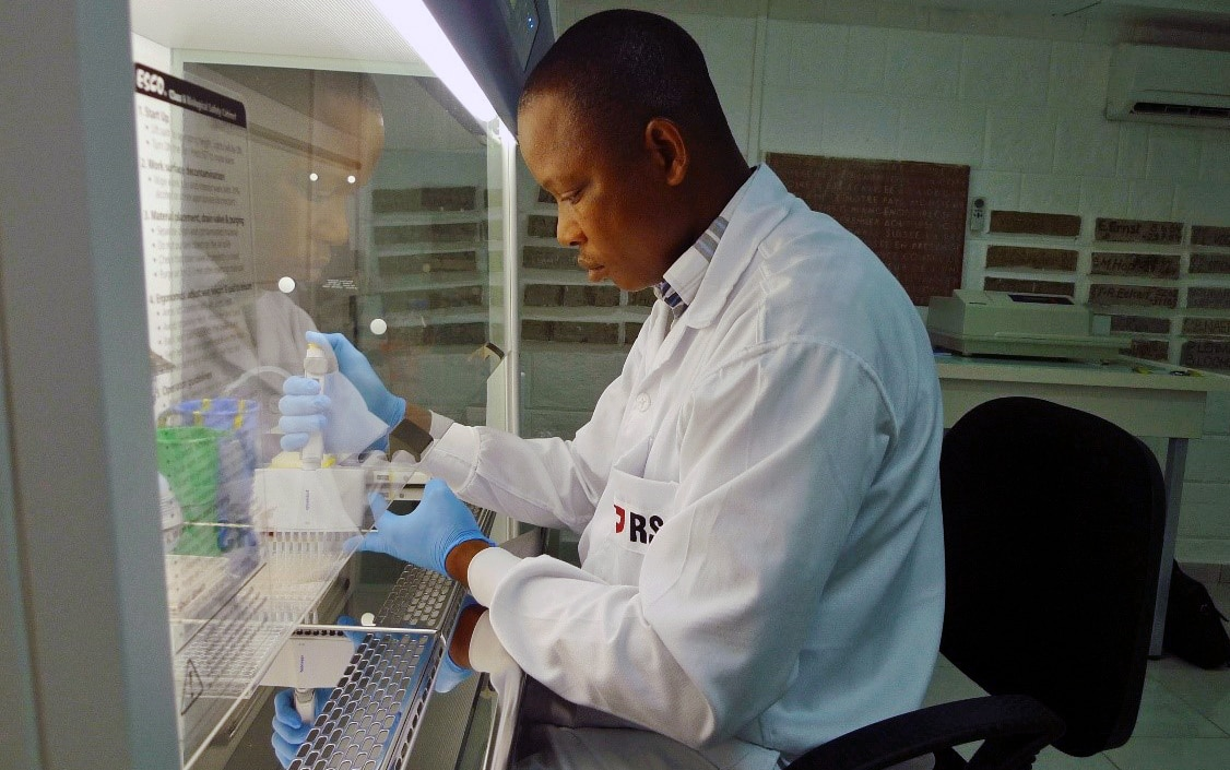 A researcher in a laboratory carries out analysis under a microscope