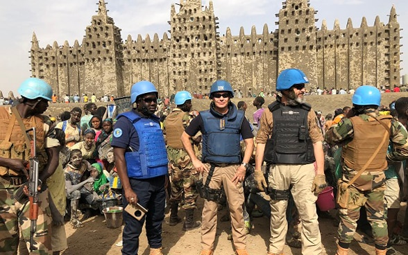 Photograph of UN police officers standing in front of the Great Mosque of Djenné in Mali while on patrol in the city.