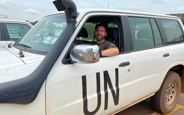 A male UN police officer at the wheel of a white car marked 'UN'.