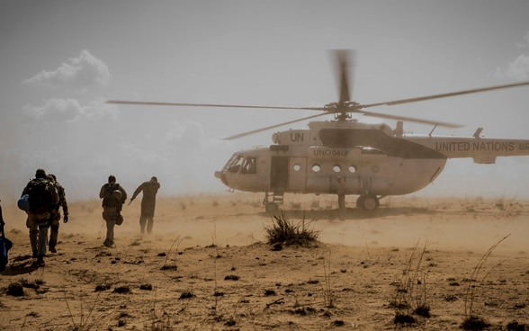 People running towards a UN helicopter landing in a dusty field in central Mali