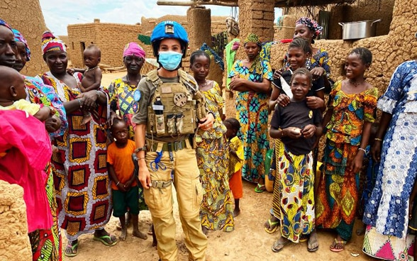 Photograph of a woman police officer wearing a face mask surrounded by Malian women and children  in a village in the Mopti region