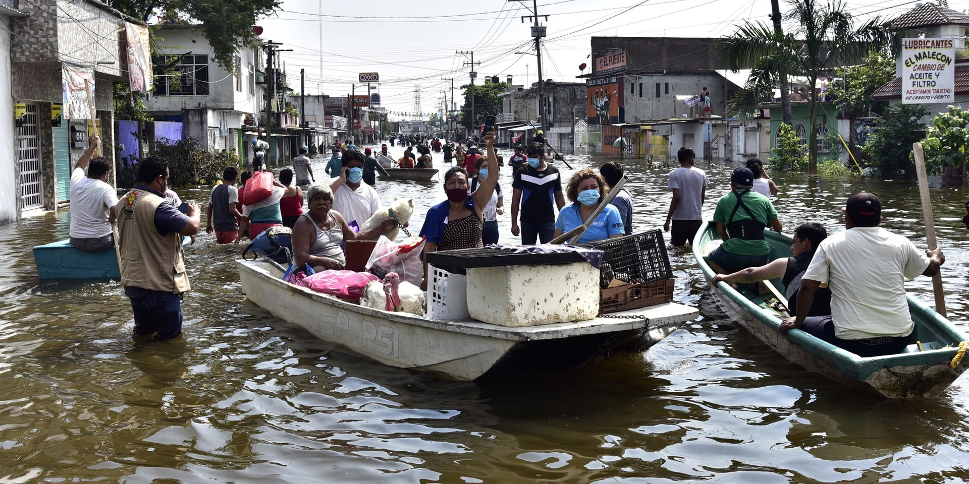 Inhabitants crossing an avenue flooded by heavy rains following the passage of hurricane Eta