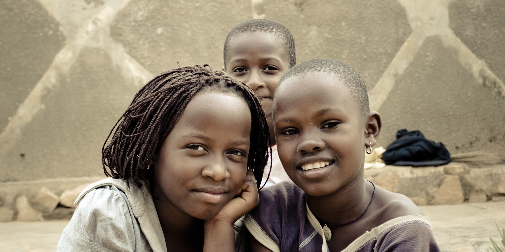 Three street children posing for the camera in Kampala, Uganda.