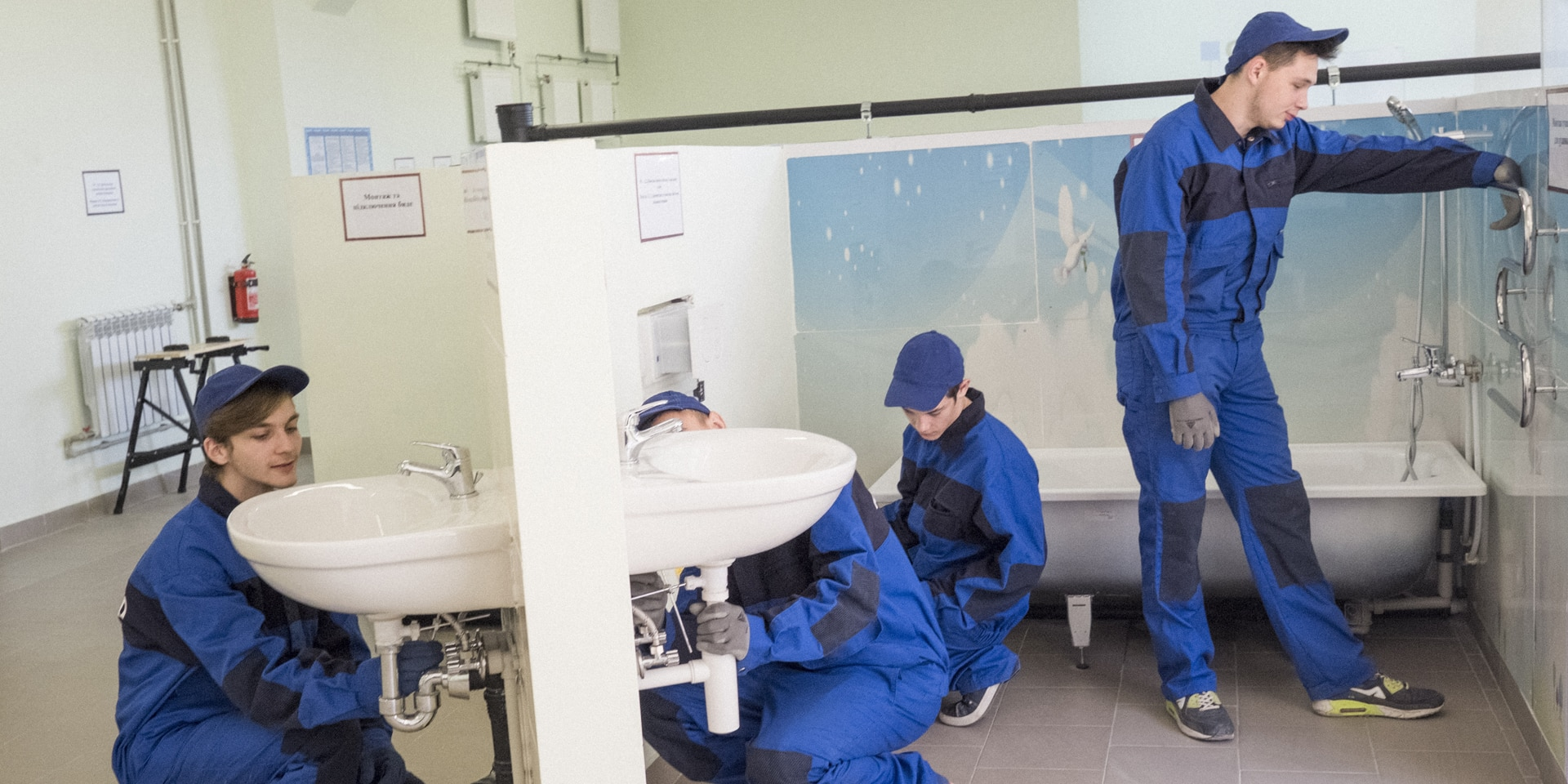 Four trainees installing sanitation facilities in a vocational school training environment in Ukraine.