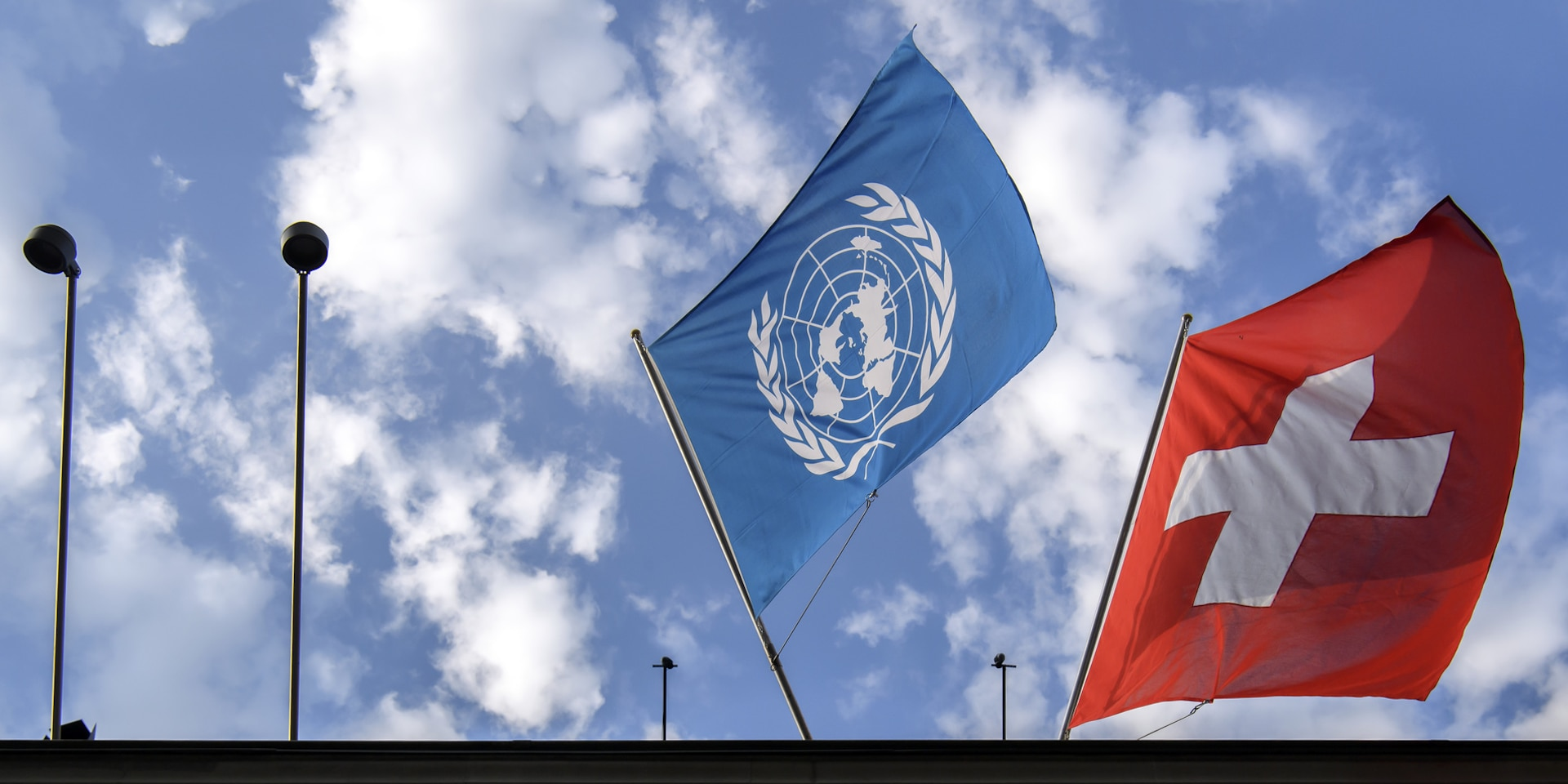 The UN flag, on the left, and the Swiss flag, on the right, flying above the Federal Palace.