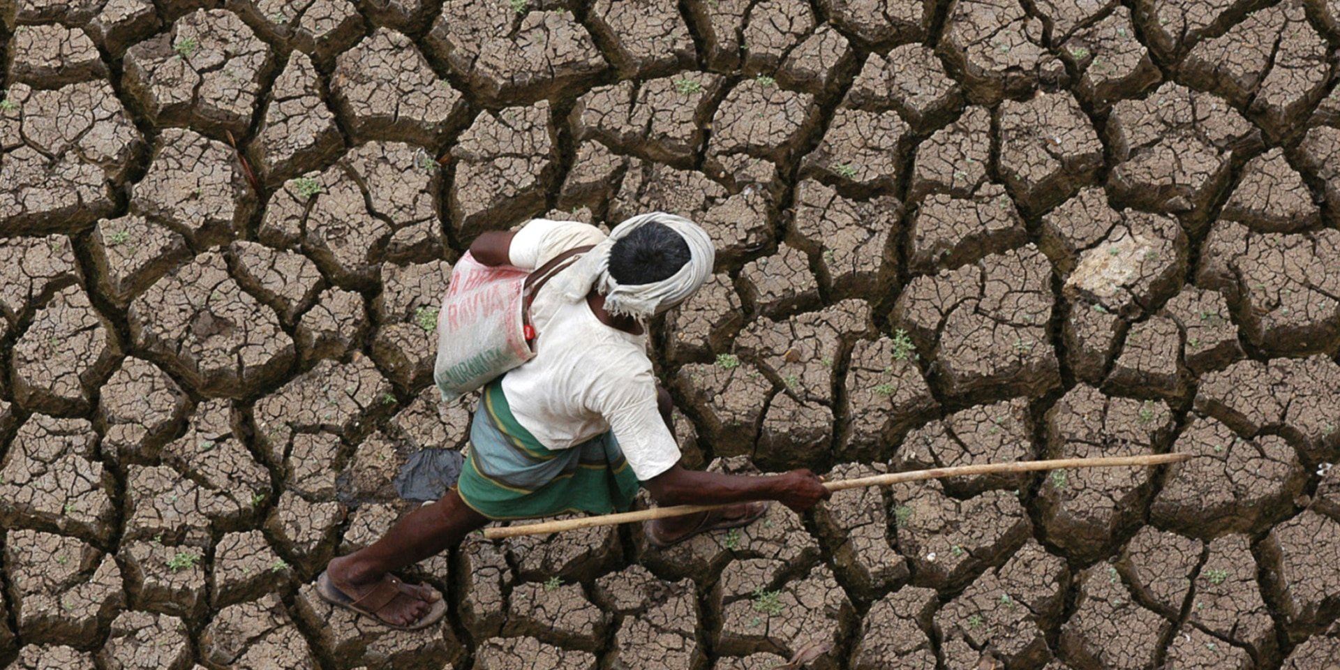A man walking across a parched field.