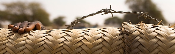 Hand of a child appearing behind the barbed wire fence of a camp for internally displaced persons (IDPs) in North Darfur