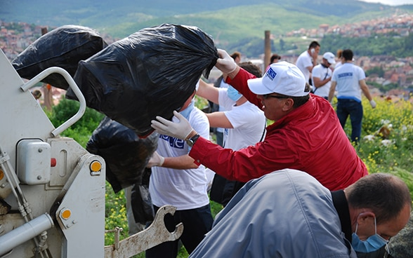 Rubbish collected in the natural surroundings of Pristina is disposed of by members of the OSCE mission