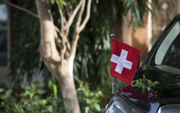 A car with a Swiss flag as a symbol for the go-between role of Switzerland as a protecting power.