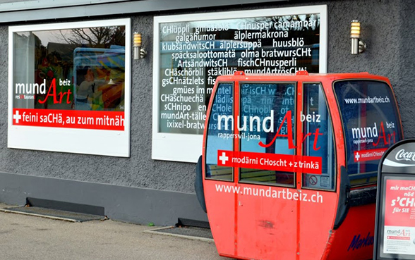 A restaurant window advertising dishes in Swiss German dialect.