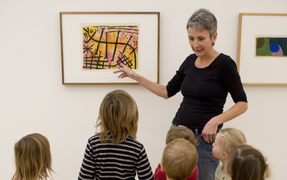 A woman explaining a picture to a group of children