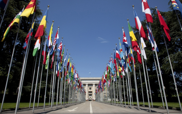 View of the United Nations building in Geneva with the flags of different countries