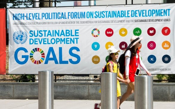 Tourists walking in front of a poster advertising the High-level Political Forum.