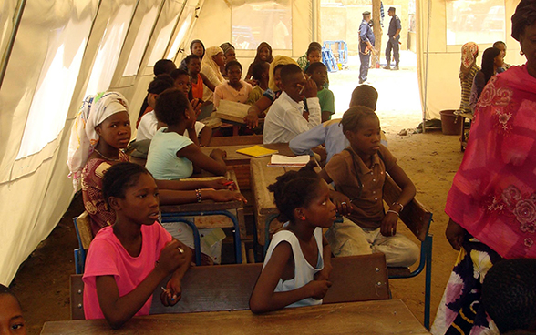 Children sitting at school desks inside a large tent.