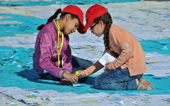 Two Moroccan girls on their knees sticking cards to the ground with a glue stick.