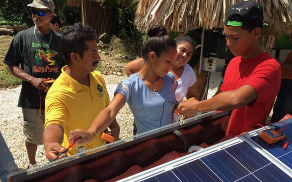 ZENNA staff training a group of people in Belize in the use of solar systems.