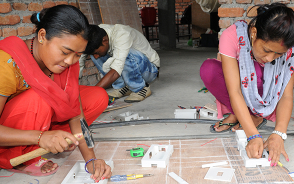 Two Nepalese women working on an electrical model.