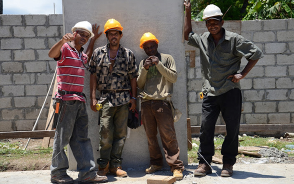 Four Haitian workers pose for a photograph on the building site. © SDC