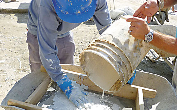 Two workers pour cement into a wooden mould.