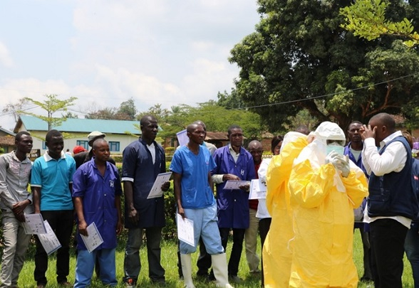 a group of health workers listen to the trainer's instructions, assisted by two individuals wearing protective clothing.