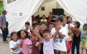 Filipino children are gathered in front of a tent provided by the Swiss Humanitarian Aid