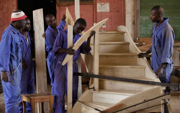 A group of young apprentices building a wooden staircase.
