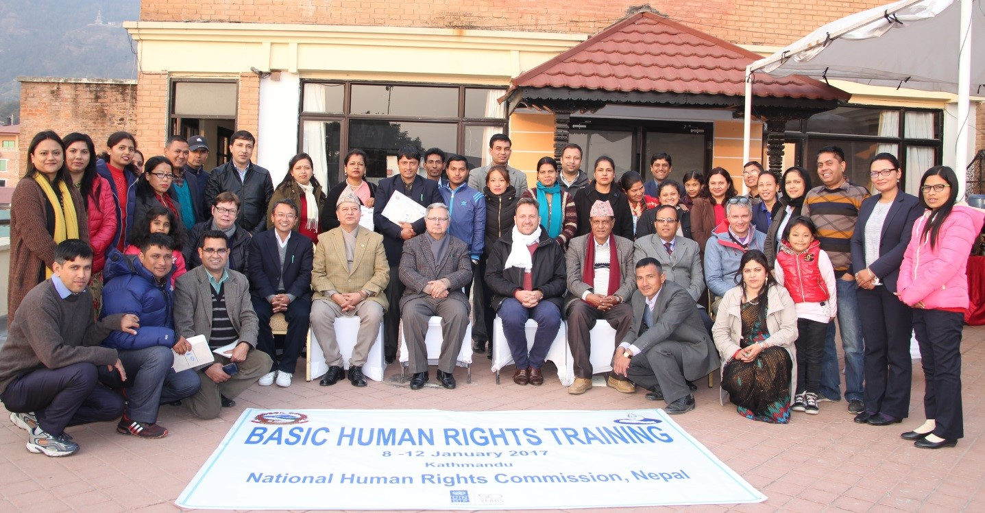 A group of women and men pose for a photo in front of a banner reading 'Basic Human Rights Training'.