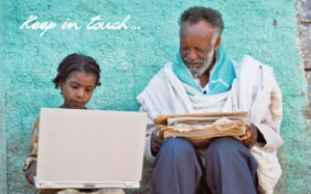 A young african girl holding a laptop and an old man holding newspapers, sitting next to each other.