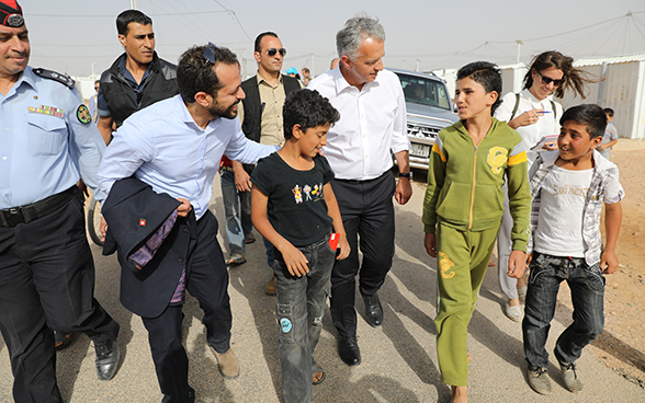 Didier Burkhalter walking through the Azraq camp accompanied by officials and young refugees